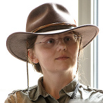 A headshot of a white middle aged woman wearing a big brown hat.