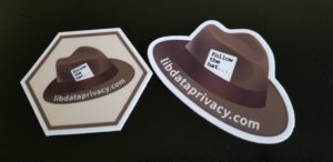 Two stickers: one hexagon sticker with a brown hat, and the other a brown hat.