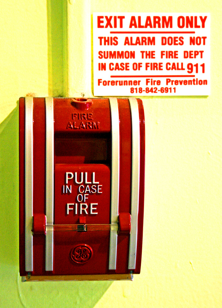 "A pull fire alarm with a sign next to it stating ""Exit Alarm Only - this alarm does not summon the fire dept In case of Fire call 911"""