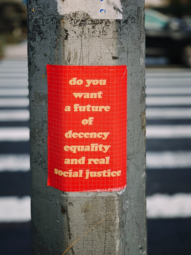 """A red sticker on a metal utility pole reads """"do you want a future of decency, equality, and real social justice"""""""