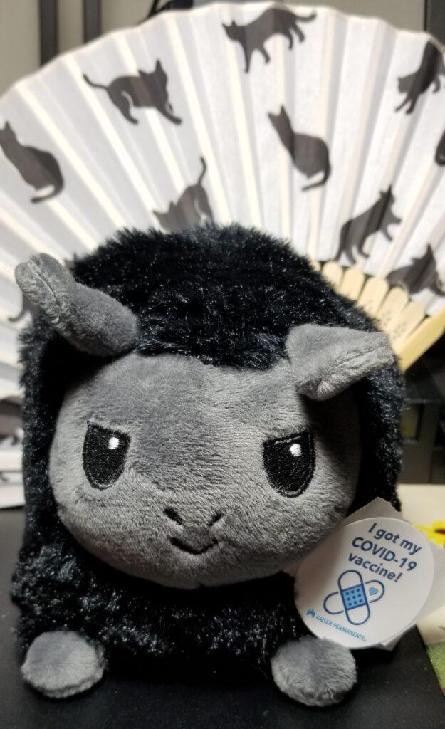 "A black plushie llama wearing a ""I got my COVID-19 vaccine!"" sticker."