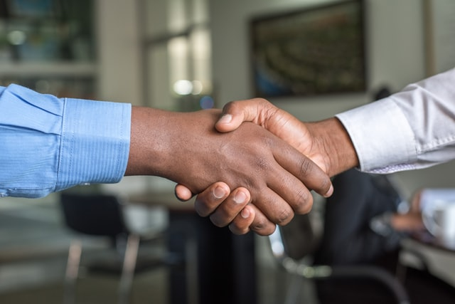 A handshake between two people in an office setting.