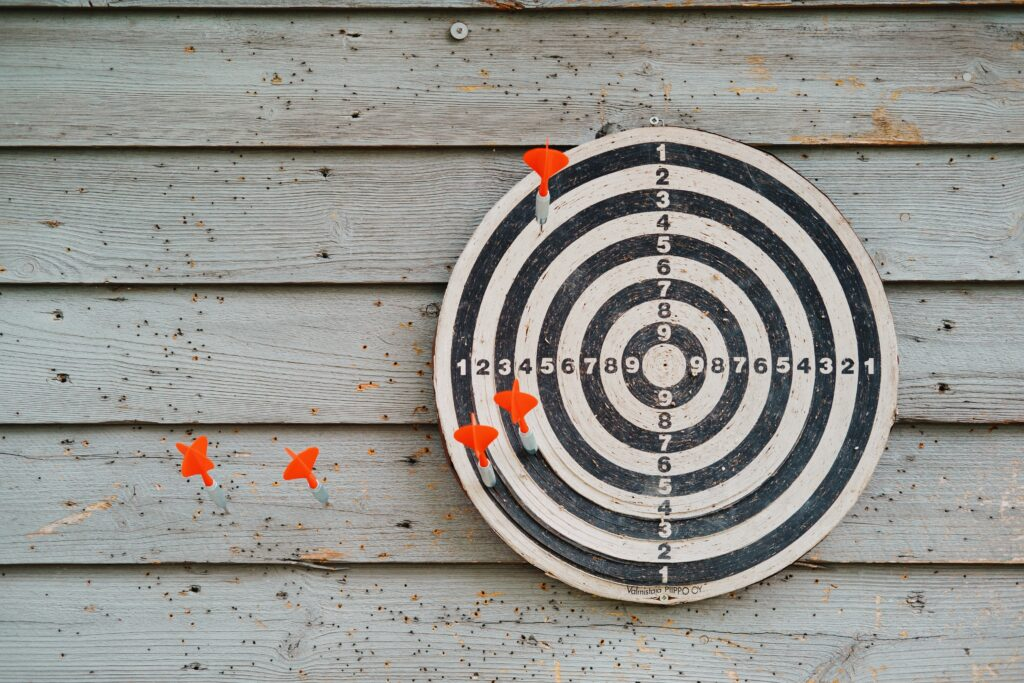 A black and white dart board hanging on a wall of wooden shingles. Three orange darts are on the board's three outermost rings (1, 2, 3) and two orange darts are embedded into the wall to the left of the board.