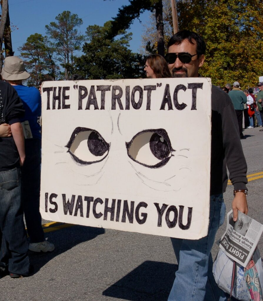 """A man wearing sunglasses holds a white sign as he walks through a street protest. The sign has two human eyes looking up and to the right. The sign message - 'The """"Patriot"""" Act is watching you"""""""