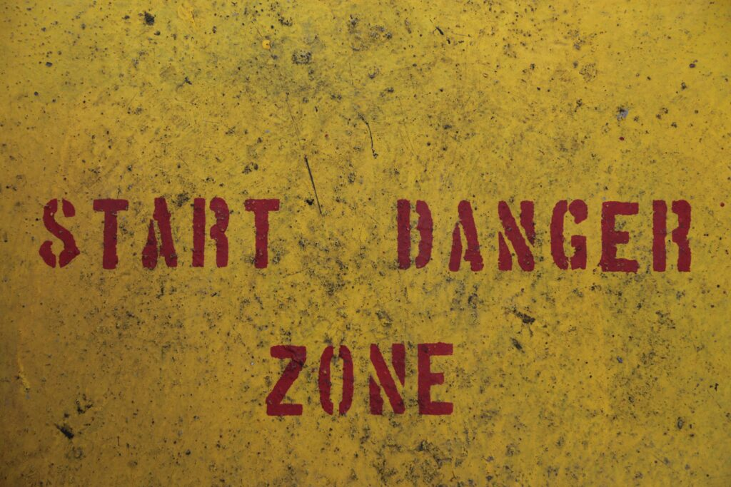 """Red spray painted text on a yellow metal background - """"START DANGER ZONE""""."""